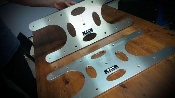 Festebraketter frest ut i aluminium. Vises frem på et bord.